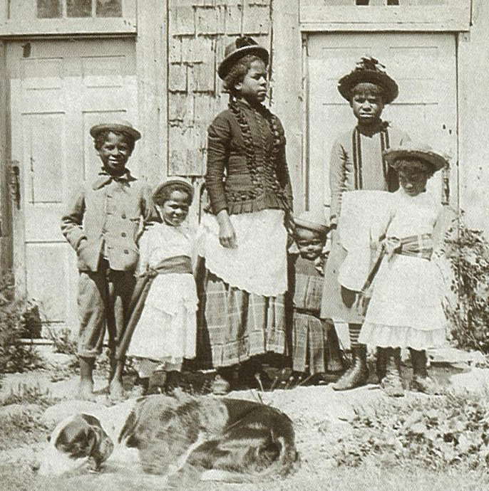 Brewster family standing in front of the Sears house.